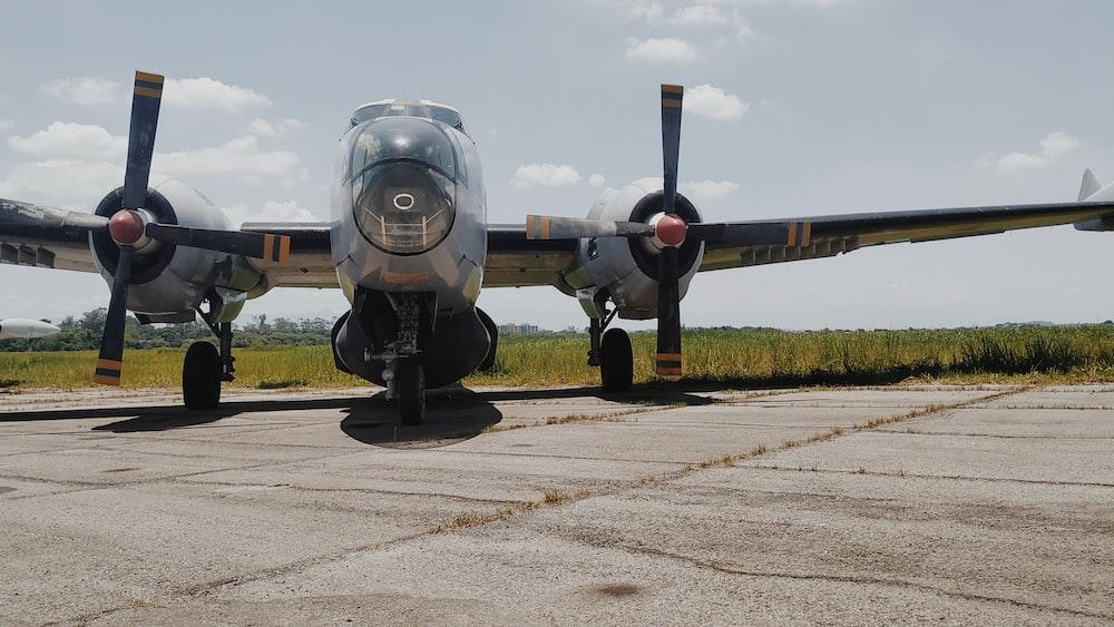 grey twin engine bomber plane on tarmac under cloudy sky