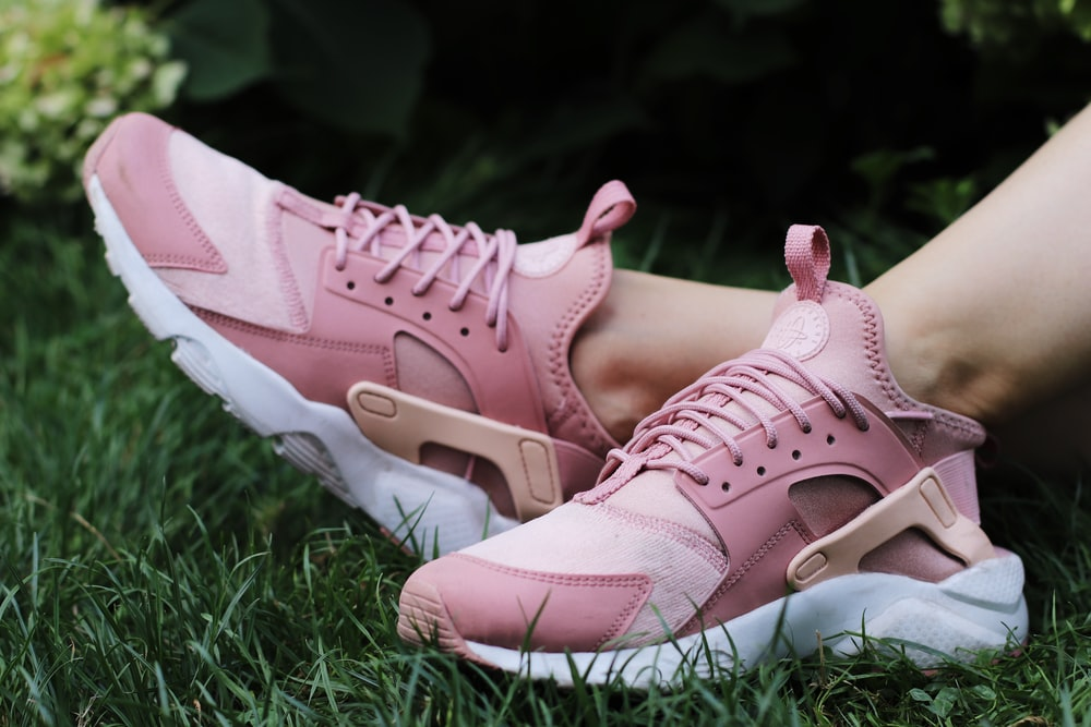person wearing pair of pink lace up low top sneakers