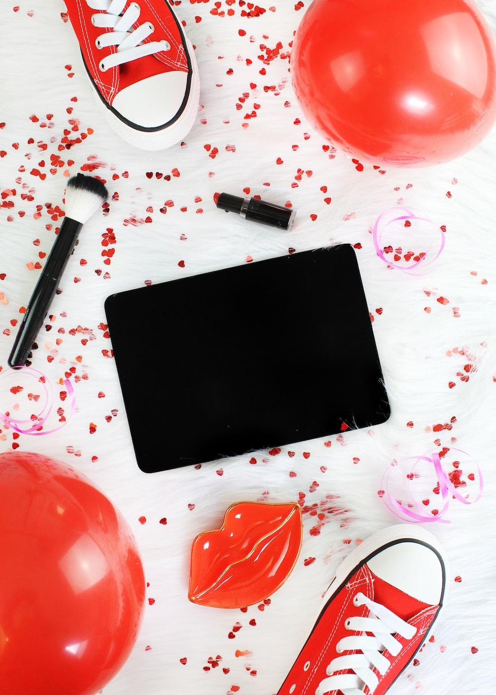 black tablet computer, makeup brush, lipstick, and balloon on floor