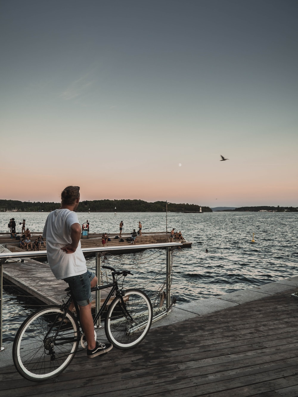 man riding bicycle while watching people on dock during daytime
