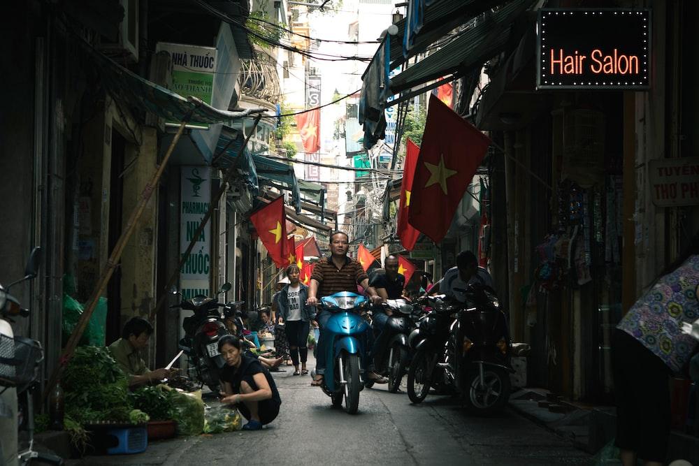 woman driving motorcycle between buildings during daytime