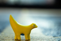 yellow plastic toy on gray pavement in close-up photo