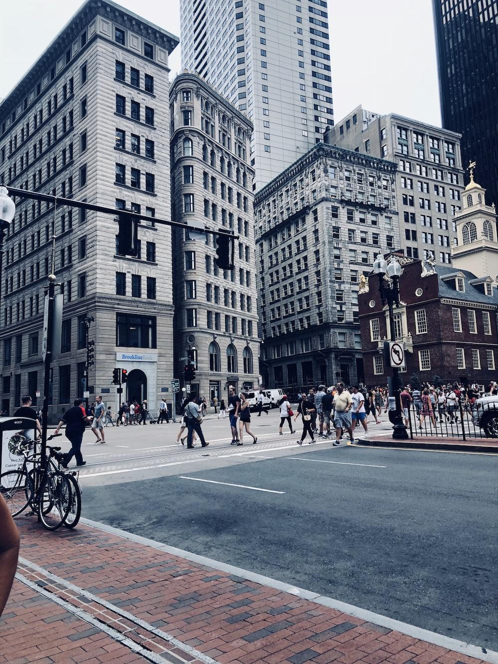 people walking on street crossing near grey tall buildings