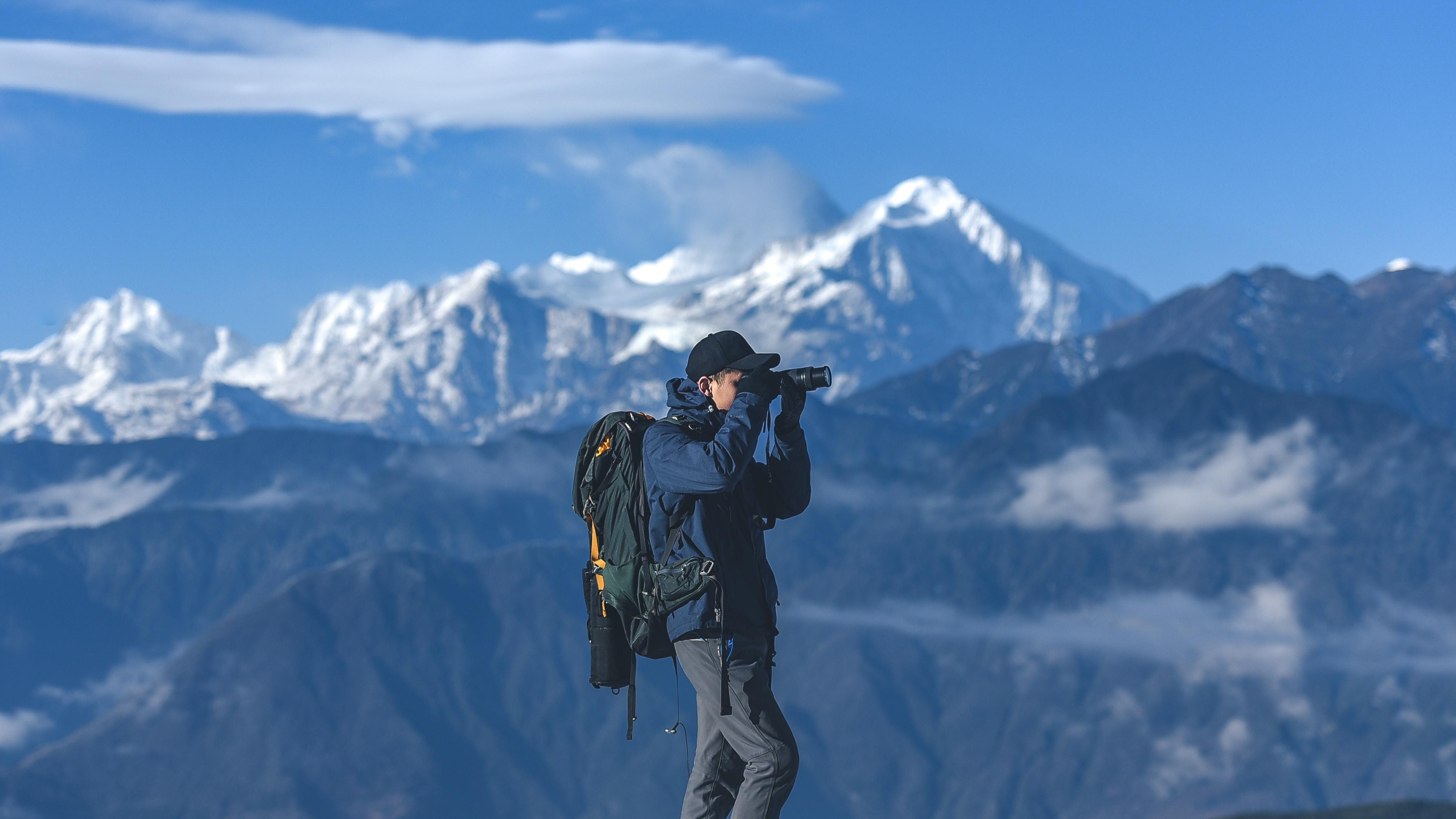 man standing on top of mountain holding binoculars