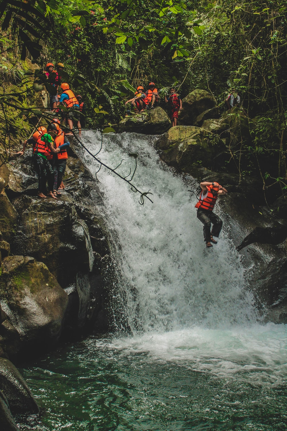 person wearing personal floating devices jumps beside waterfalls