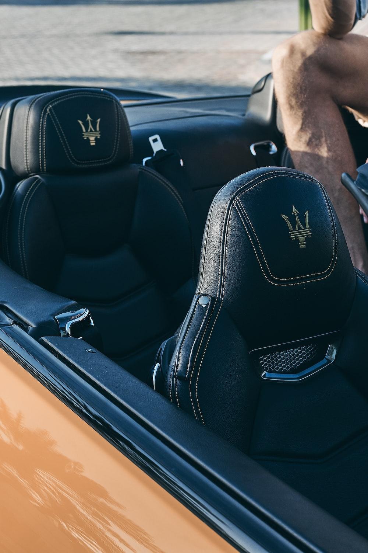 person sitting on Maserati convertible vehicle during daytime