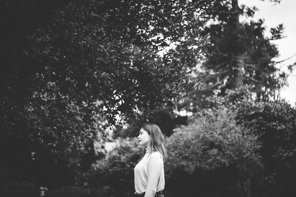 grayscale photography of standing woman in long-sleeved shirt beside tree