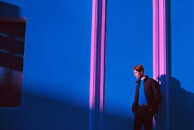 man in black full-zip jacket standing near blue wall surrealism zoom background