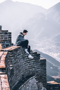 man sitting top of wall