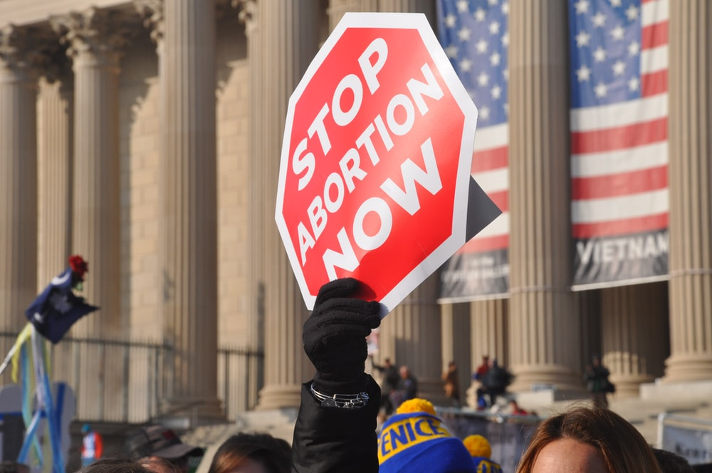 person holding red Stop Abortion Now signage