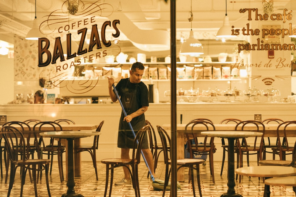 man mopping floor of Coffee Balzac's roaster