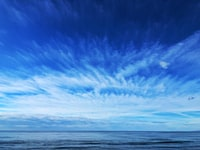 calm sea under blue and white skies