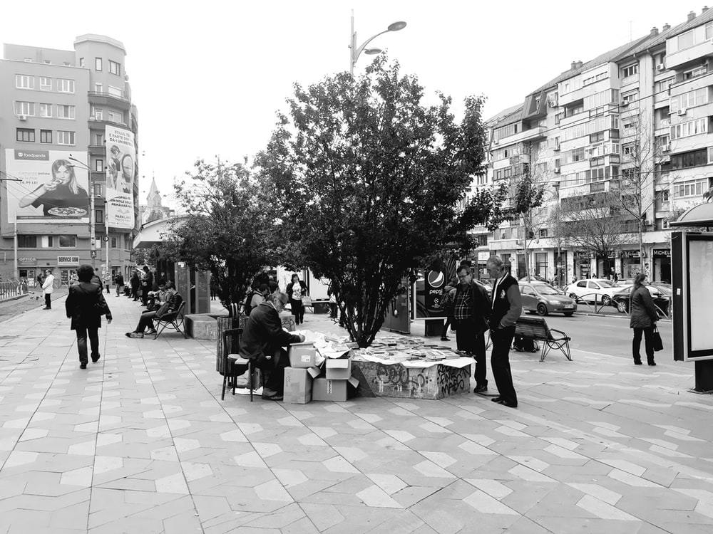 greyscale photo of people standing and sitting on pavement near tree during daytime