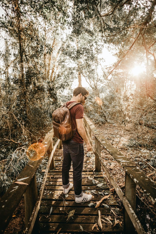man standing on brown wooden pathway