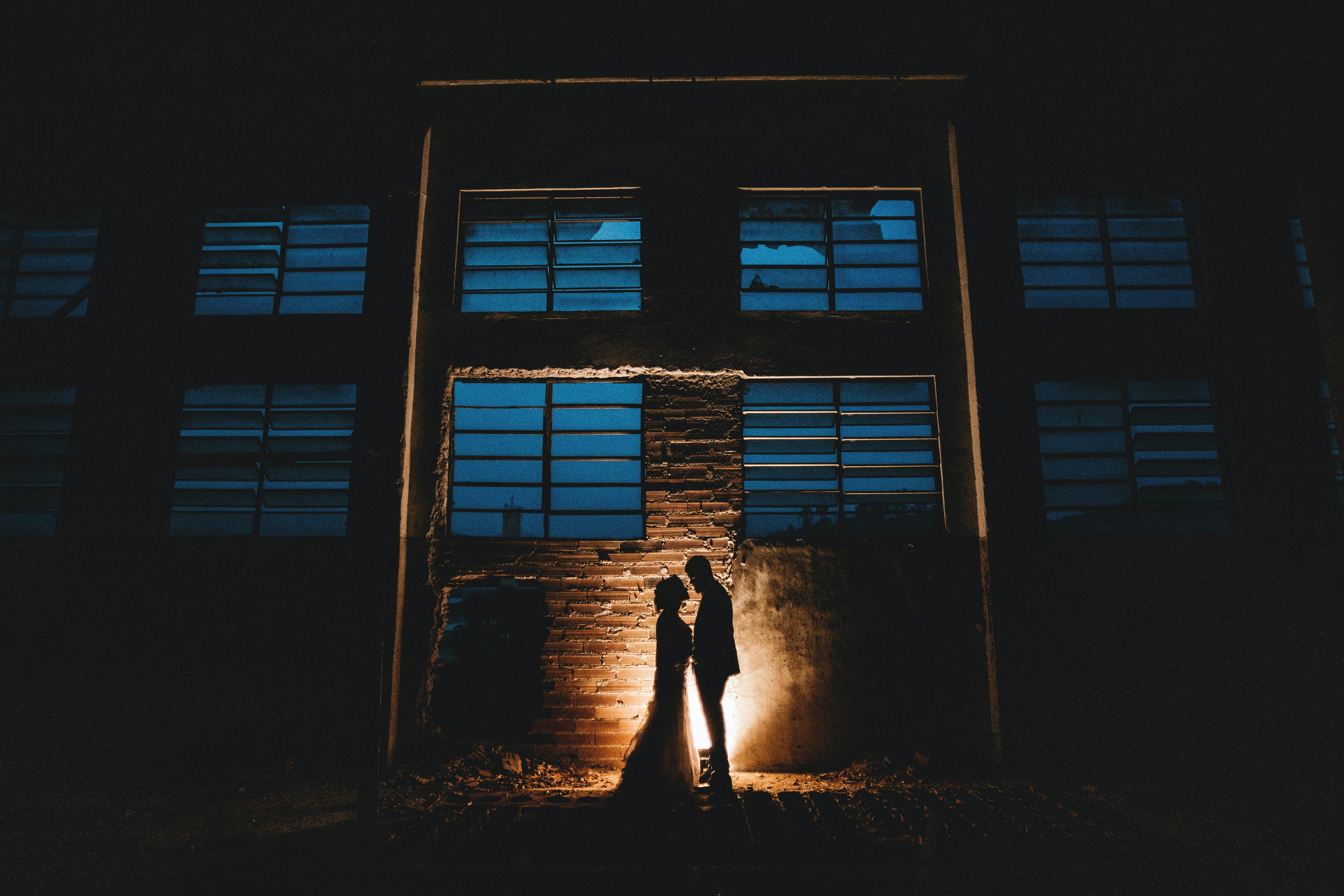 silhouette of man and woman standing beside building