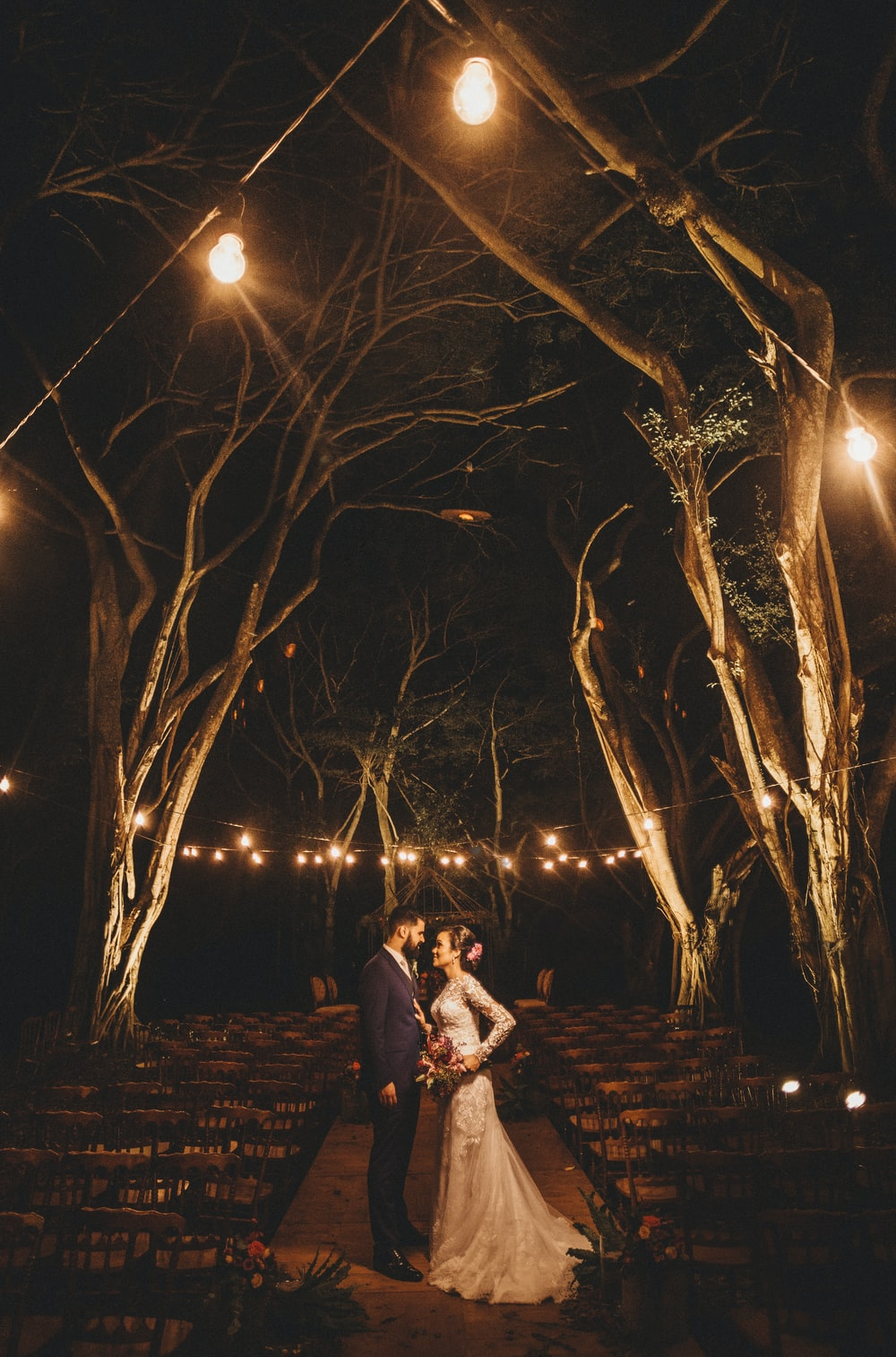 couple under lighted tree during night time