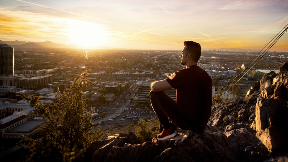 golden hour photography of man sitting on rock