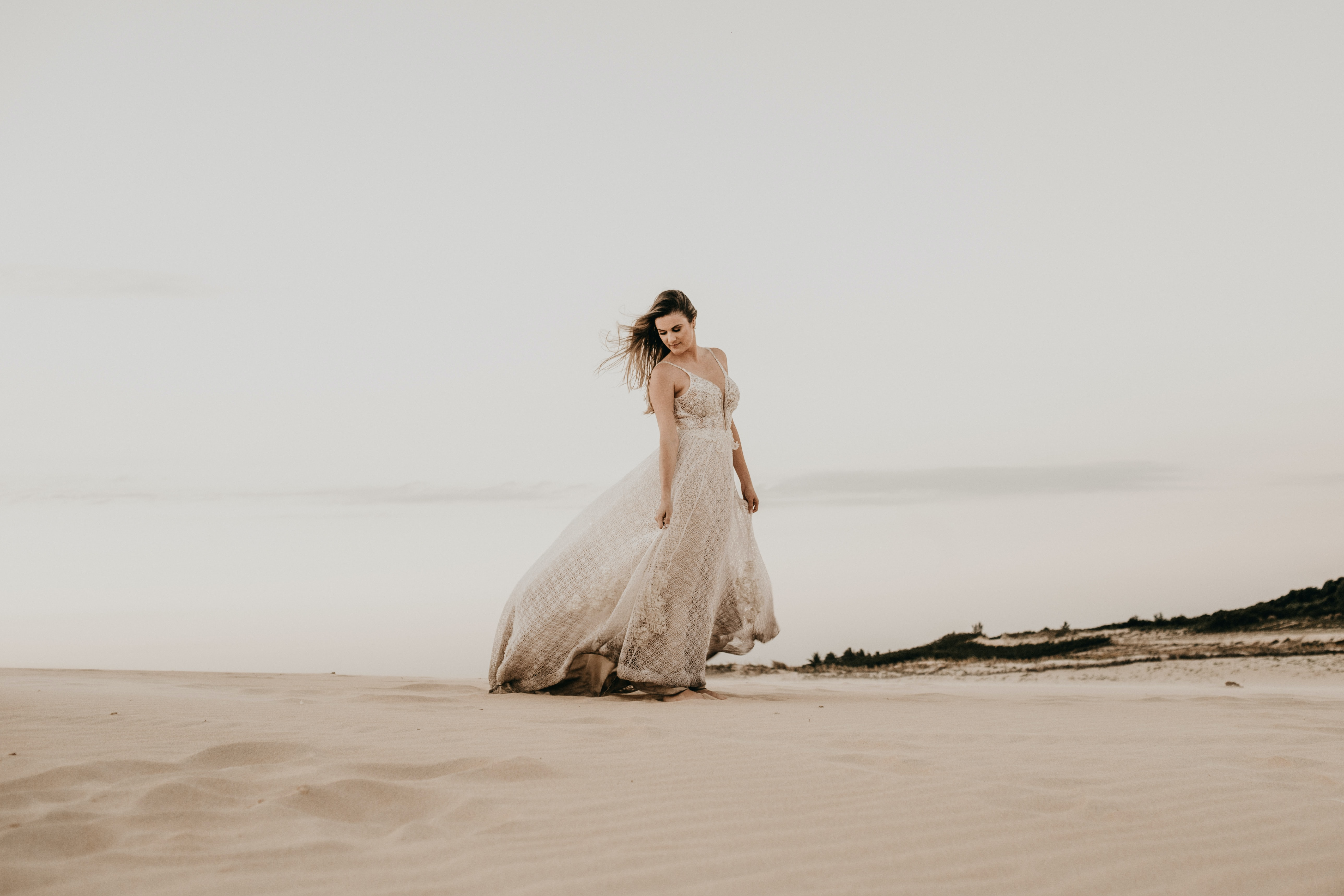 woman wearing white gown standing on sand during daytime