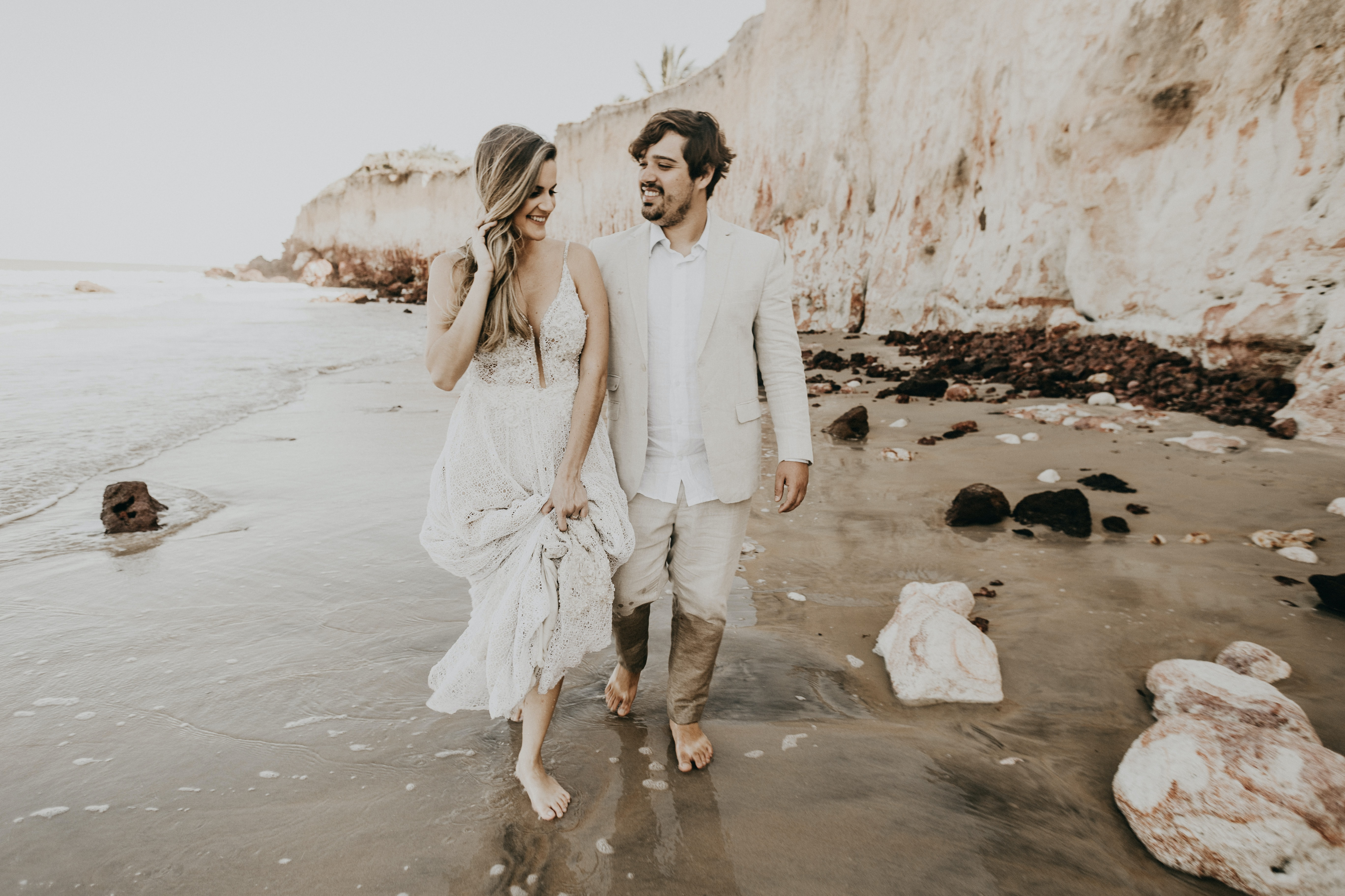 couple walking on the beach with trash during daytime