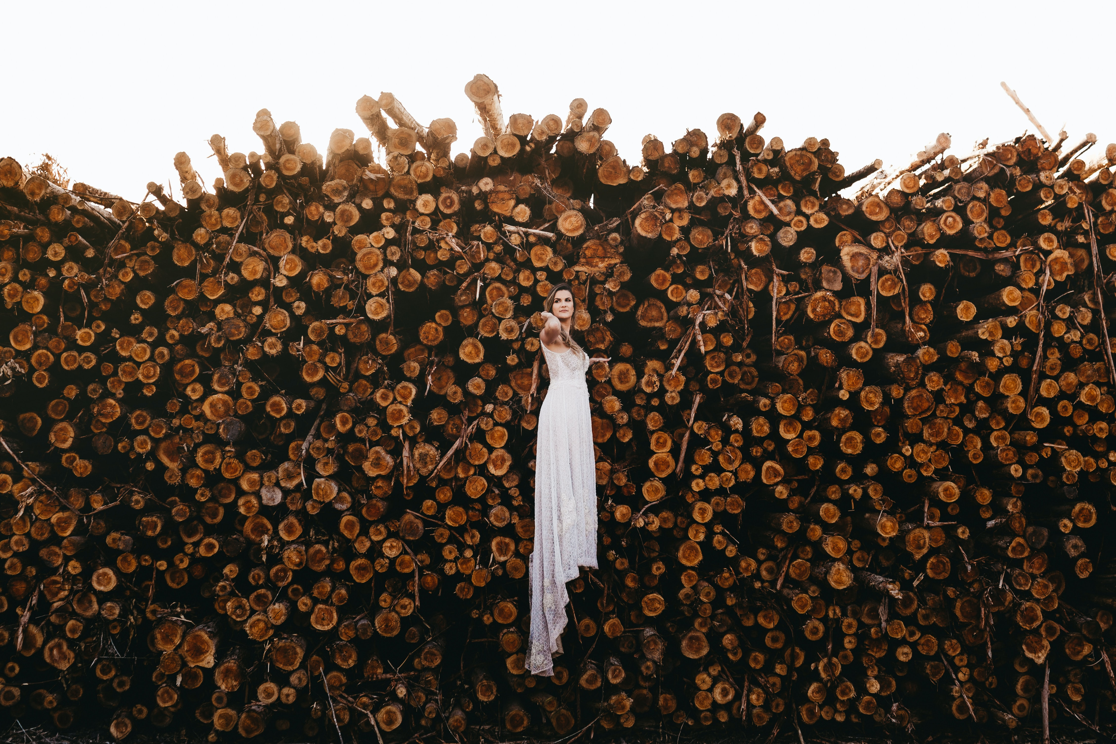 woman standing in front of wood logs