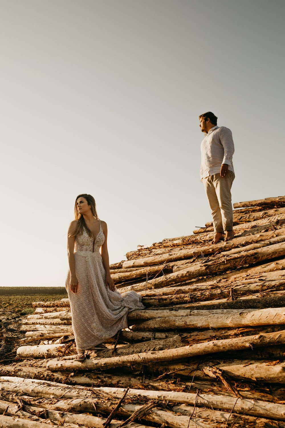 man and woman standing on pile of wood logs