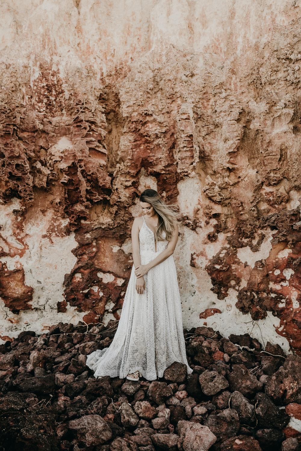woman in white dress standing under mountain