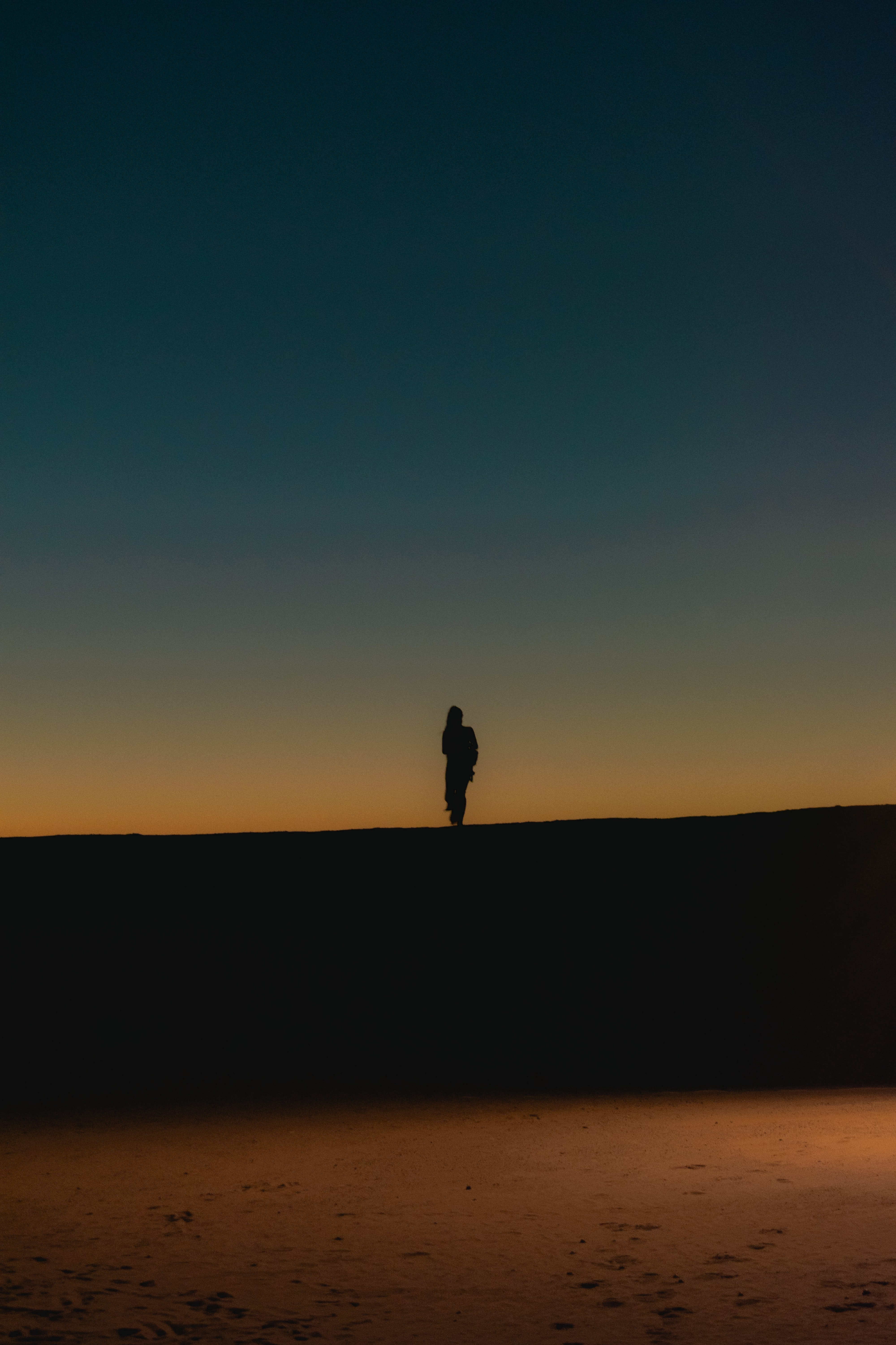 silhouette of person standing on black surface