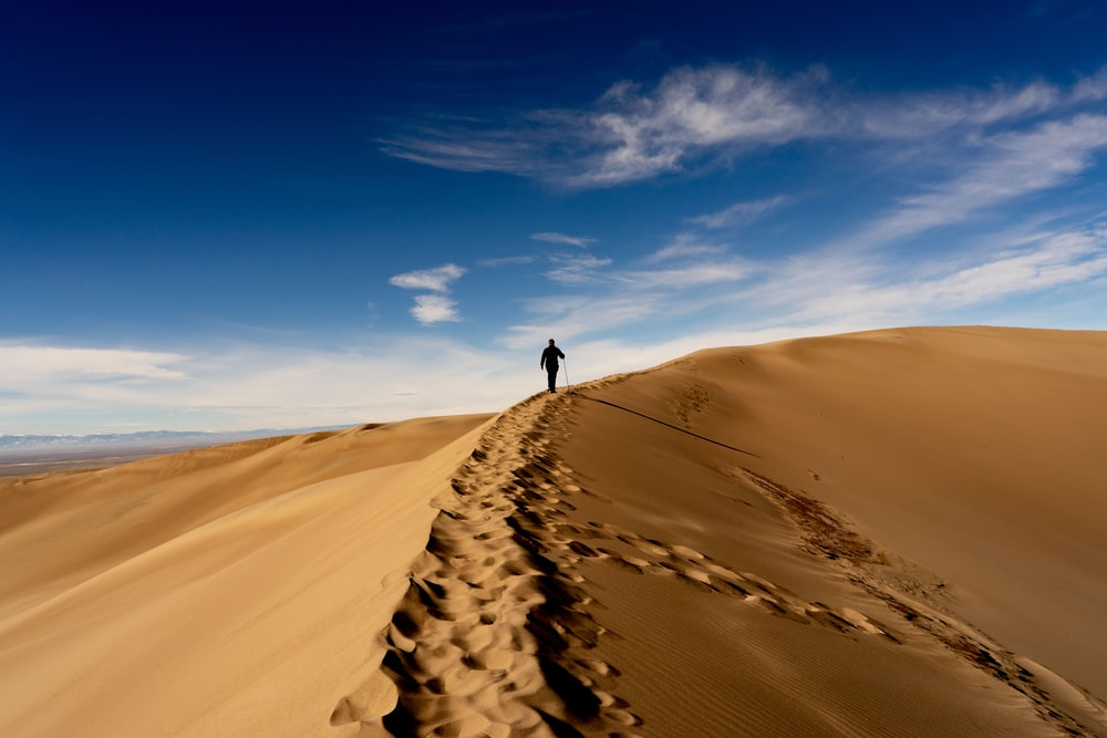 man waking on sand dune on desert under blue and white cloudy sky