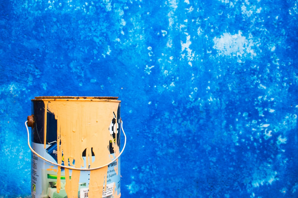 yellow paint can beside blue wall