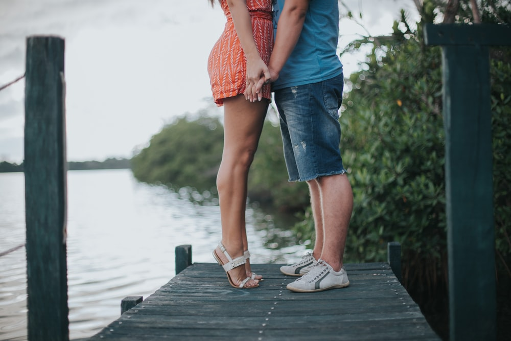 man and woman holding hands standing on gray wooden dock during daytime