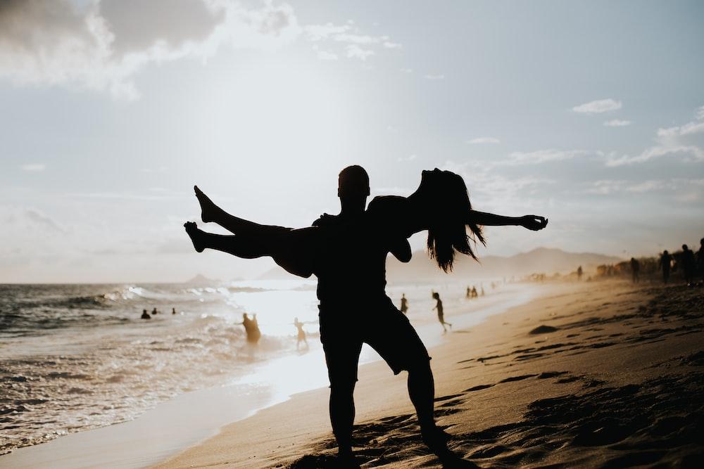 man lifting woman near ocean
