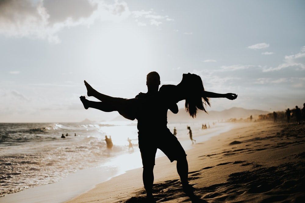 man lifting woman near ocean