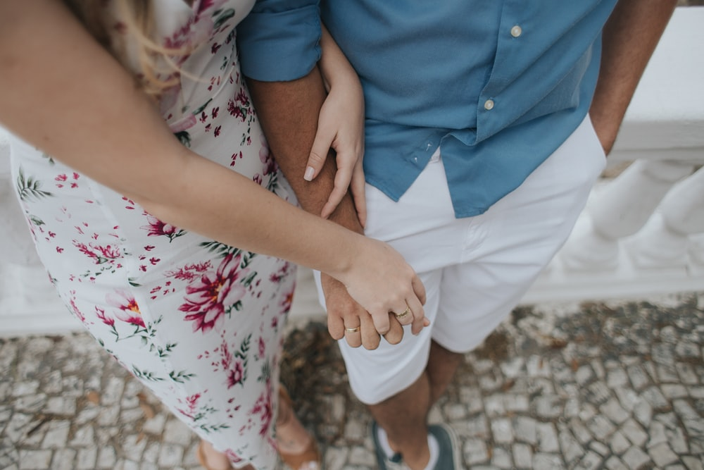 woman holding hands with man while leaning on wall