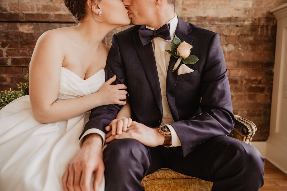 sitting bride and groom kissing