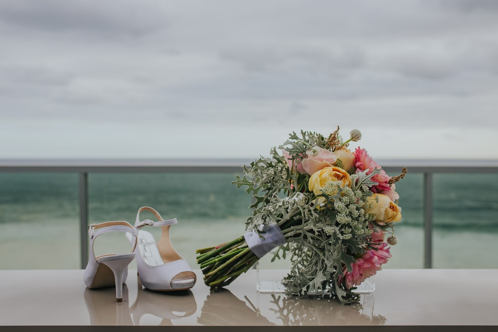 bouquet of flowers near white leather heeled sandals viewing calm body of water