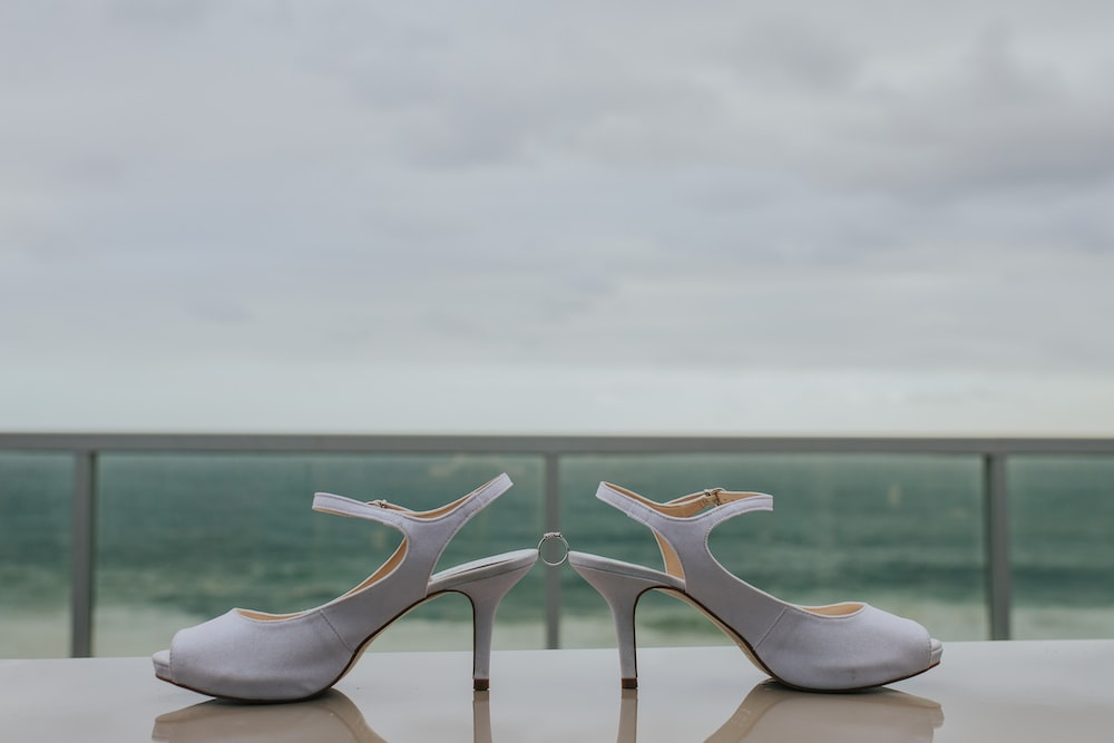 pair of grey leather strap heeled shoes on table fronting the sea
