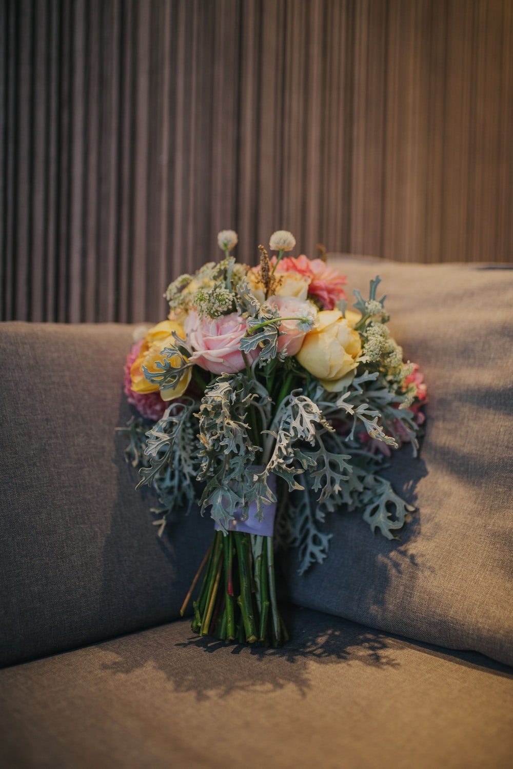 bouquet of rose flowers on gray sofa inside room