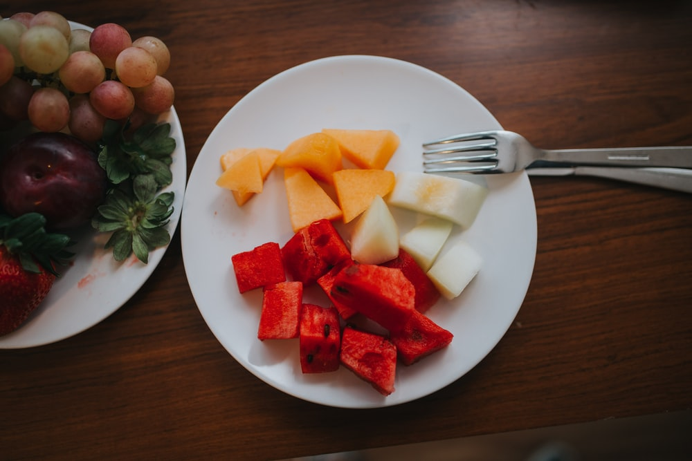 sliced watermelon and mango on plate with fork