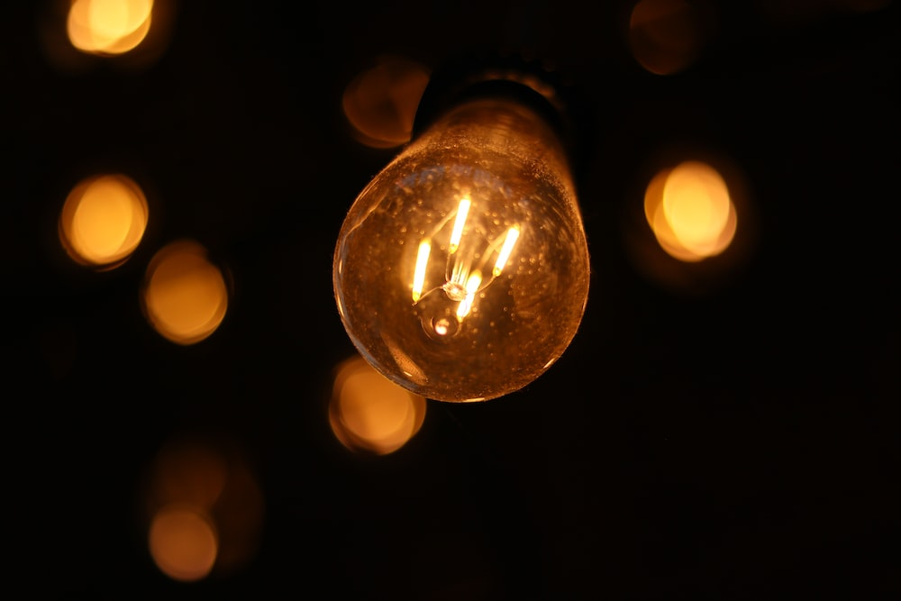 bokeh lights photography of filament light bulb at night