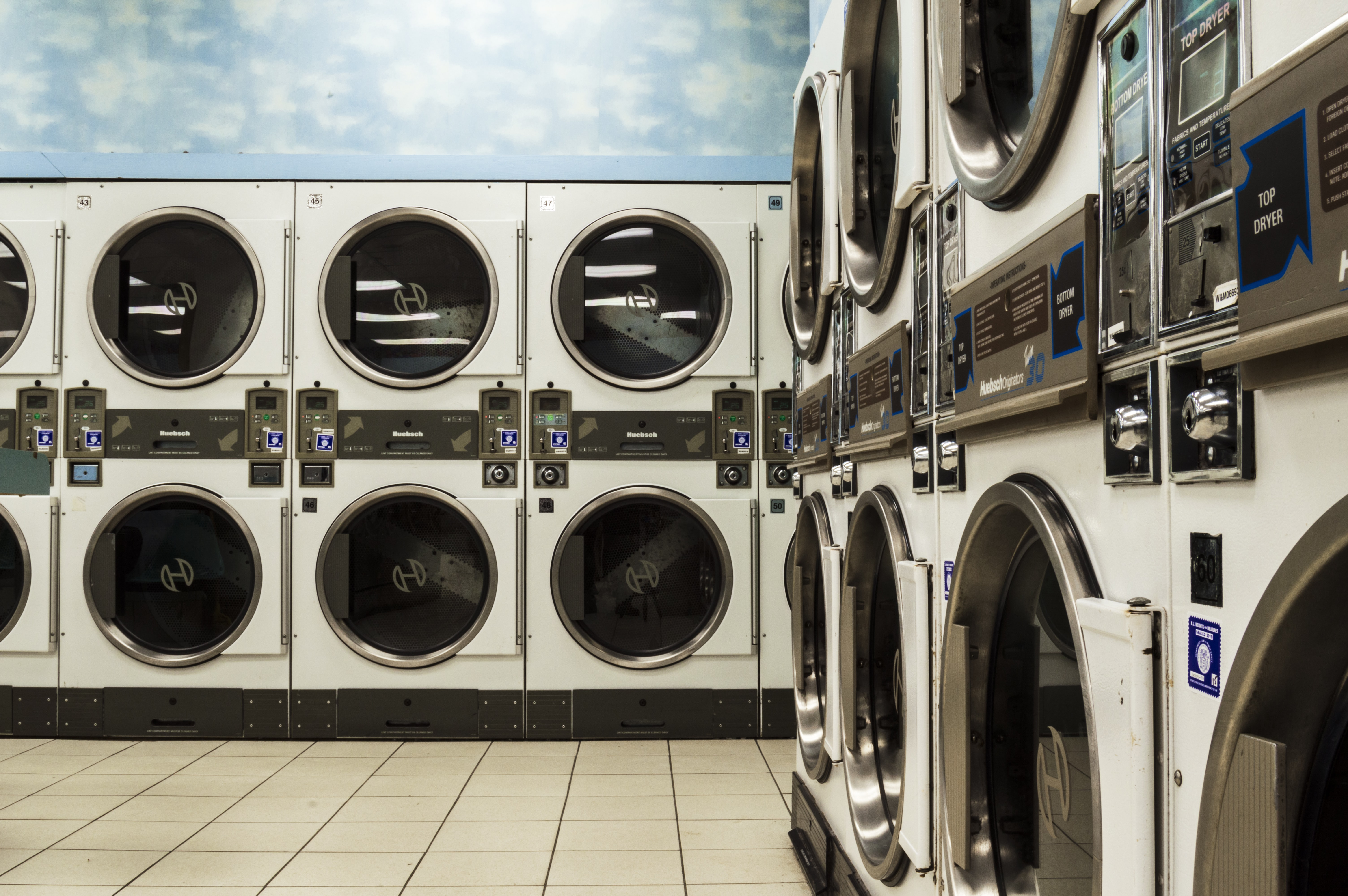 white washer and dryer laundry centers on white floor tiles