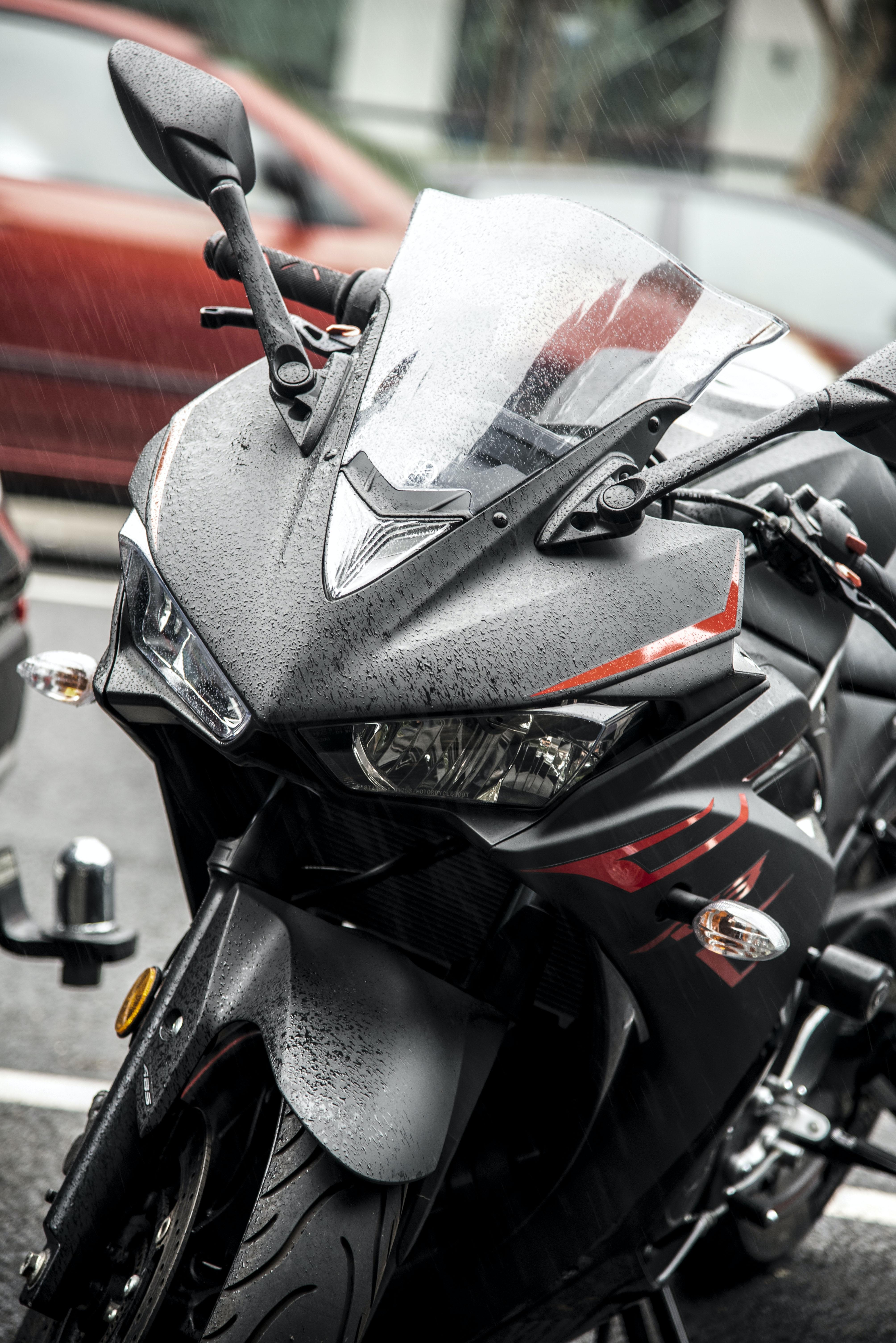 black and red Yamaha R1 sports bike near parked car