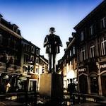 man standing statue in between buildings