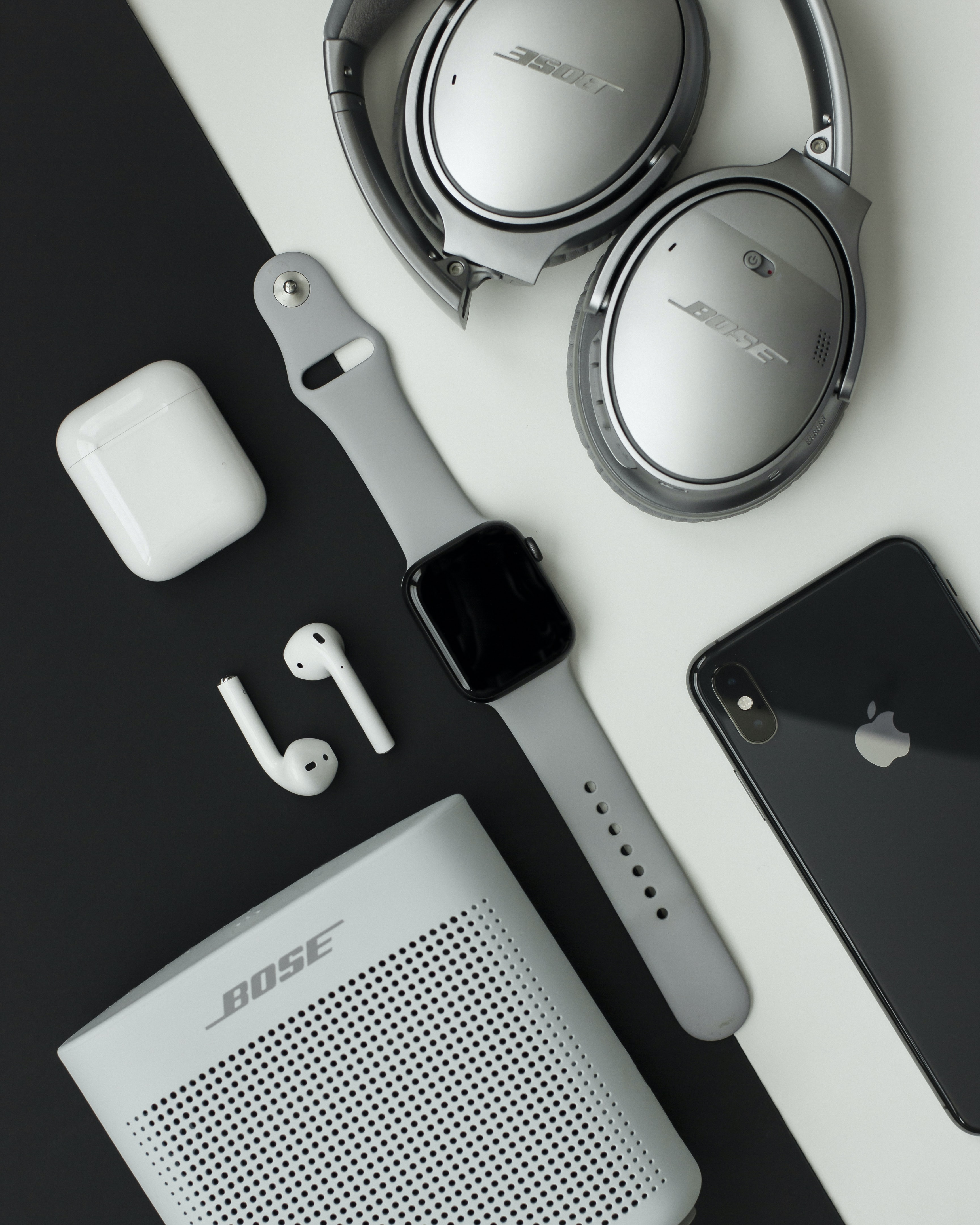 gray Bose headphones, Apple Watch and iPhone on white and black surface