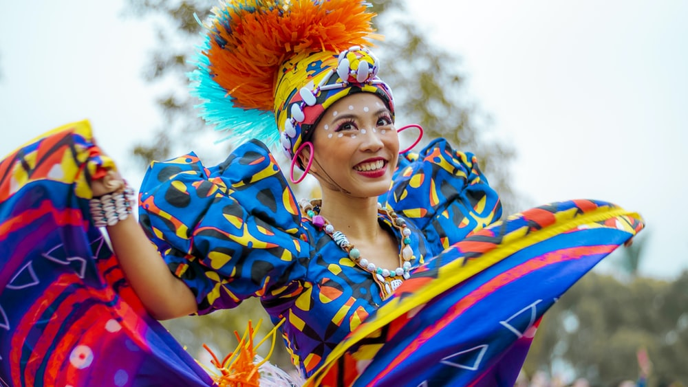 smiling woman wearing multicolored dress dancing outdoor during daytime