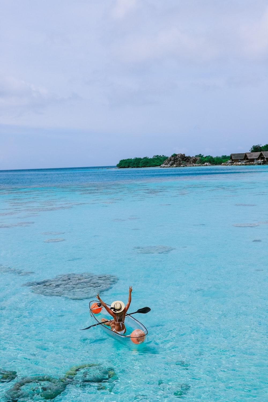 woman at shallow sea water riding transparent boat
