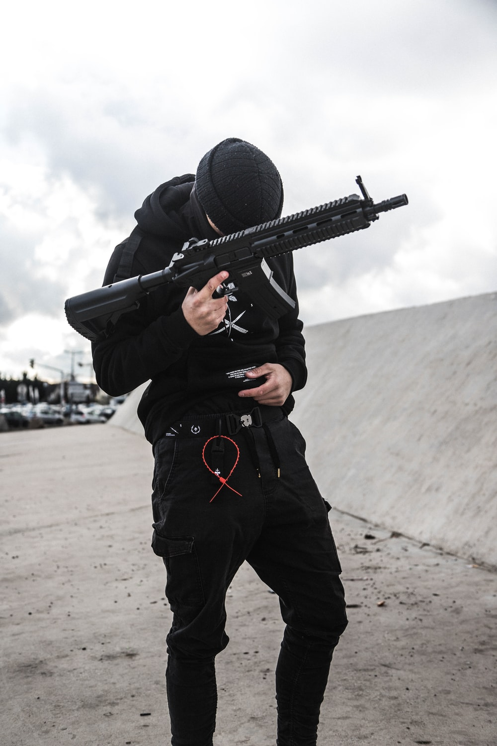 standing man in black hoodie and black pants holding assault rifle during daytime