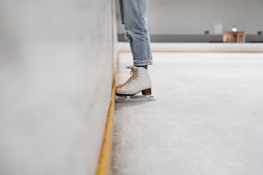 person wearing white and gray skate shoes inside ice skating rink
