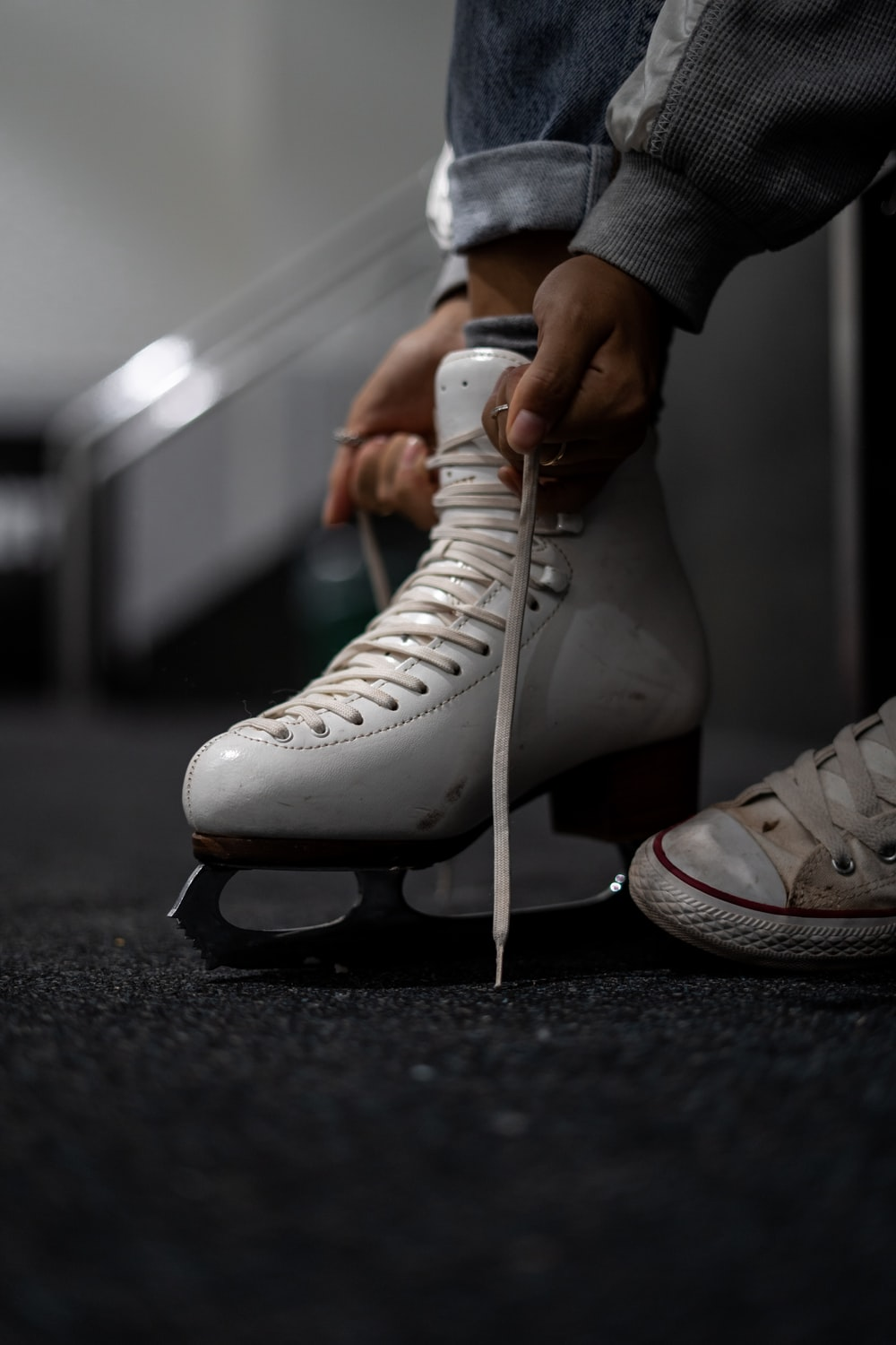 person wearing white leather ice skate