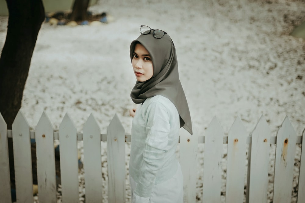 woman wearing gray hijab standing beside white fence