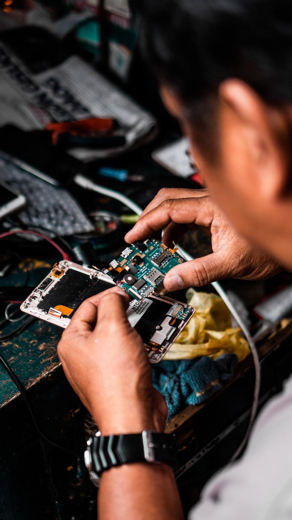 man repairing Android smartphone